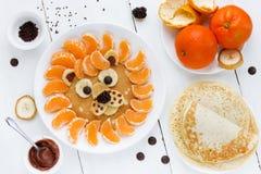 Lion pancake with tangerines chocolate banana berry. Fun food fo Royalty Free Stock Image