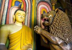 A lion prays before a Buddha statue inside the main Image House at Wewurukannala Vihara. Stock Photo