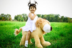 Lion ride. Little girl riding on her big lion animal in a great grass field Royalty Free Stock Photo
