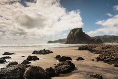 Lion rock of Piha Beach behind dispersed rocks. Auckland, New Zealand - March 2, 2017: Lion rock on Piha Beach of Tasman Sea surrounded by surf and under blue royalty free stock photo