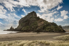 Lion rock on Piha beach fills full frame. Auckland, New Zealand - March 2, 2017: Lion rock on sandy Piha beach of Tasman Sea fills full frame under blue sky stock photography