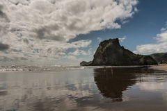 Lion Rock of Piha Beach reflected in wet beach. Auckland, New Zealand - March 2, 2017: Lion rock reflected in wet sandy Piha beach in Tasman Sea surf and under stock image
