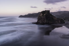 Lion Rock, Piha, NZ. Iconic Lion Rock at Piha Beach, Auckland, NZ. Long exposure used to blur out the swell stock photography