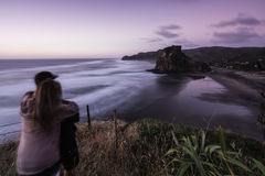 Lion Rock, Piha, NZ. Iconic Lion Rock at Piha Beach, Auckland, NZ. Long exposure used to blur out the swell stock images