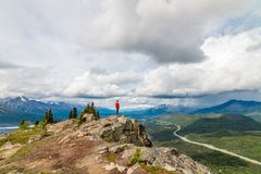 Lion's Head, Alaska. A hiker pauses for the view at the top of the rock formation, Lion's Head.  Lion's head overlooks the Matanuska River and Valley, in Alaska Stock Images