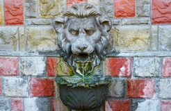 Lion's source. Spring following from a mouth of a bas-relief of a lion Royalty Free Stock Images