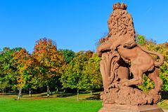 Lion sculpture in autumnal park of Phillipsruhe Castle in Hanau, Germany. Lion sculpture in English landscape park of Phillipsruhe Castle on a sunny October day Stock Image