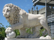 Lion sculpture made of white marble against the backdrop of the old palace Royalty Free Stock Images