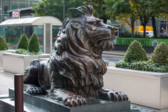 Lion sculpture by the office entrance. LONDON, UK - 7 SEPTEMBER, 2015: Canary Wharf business life. Lion by the office entrance Stock Photo
