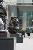 Lion sculpture by the office entrance. LONDON, UK - 7 SEPTEMBER, 2015: Canary Wharf business life. Lion by the office entrance Royalty Free Stock Photo