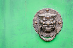 Lion-shaped door knocker against a bright green door, China Royalty Free Stock Image