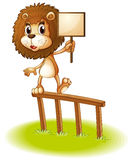 A lion standing on a wooden fence holding an empty signboard Royalty Free Stock Images
