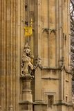 A lion stands guard before the royal entrance below the Victoria tower at the British Parliament building in London, England. A lion stands guard before the Stock Image