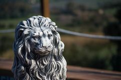 Lion statue with blur. Stone lion statue with green defocused background royalty free stock images