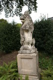 Lion statue carrying coat of arms on a plinth. Garden decoration of a statue of a lion with coat of arms on a plinth, England Royalty Free Stock Photography