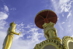 Lion statue. Golden Lion statue and Buddha statue on blue sky background Royalty Free Stock Images