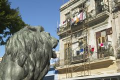 Lion statue looking at old buildings with laundry in Old Havana, Cuba Stock Photos