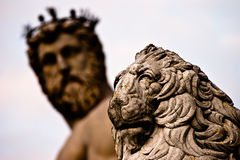 Lion statue with Neptune in background Stock Images