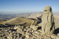 Lion statue overlooking mountains. An ancient stone statue of a lion overlooking a big dry mountainous landscape Stock Photo