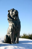 Lion Statue. A lion statue sitting proudly in the snow guarding the village entrance Stock Photo