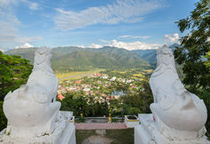 Lion statue at Wat Phra That Doi Kong Mu with city view. Back view of white lion statue at Wat Phra That Doi Kong Mu with aerial city view of Mae Hong Son Royalty Free Stock Images