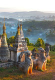 Lion statues in front of the pagoda on mountain at dawn Stock Photos
