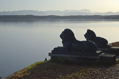 A Lion Statues with German Alps. Lion Statues with German Alps and Lake royalty free stock images