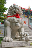 Lion stepping world as stone statue at front chinese temple Stock Image