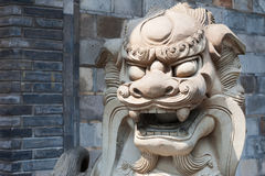 Lion stone statue head in the sun against a brick wall. China Stock Photography