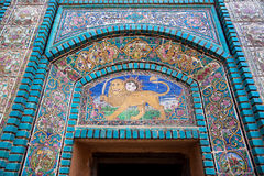 Lion with a sword and a rising sun on a fragment of mosaic tiled wall of old Persian mosque, Iran. Stock Images