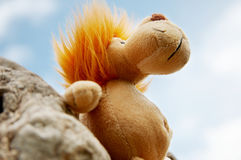 Lion toy. Standing against a stone with blue sky as background royalty free stock images