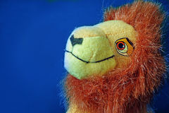 Lion toy. Close-up view of a stuffed lion on blue background Royalty Free Stock Photo