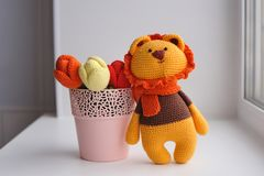 Amigurumi toy. Lion with tulips. Lion toy knitted in the technique of knitting amigurumi Royalty Free Stock Images