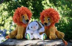 Twin amigurumi lions with a rabbit in the garden royalty free stock image