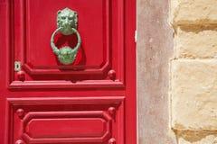 Lionheaddeurknop en rode deur Stock Fotografie