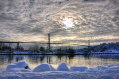Lions Gate Bridge with sun and clouds in winter. Royalty Free Stock Photo