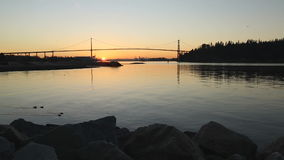 Lions Gate Bridge Sunrise, Vancouver. Dawn in Vancouver with the Lion's Gate Bridge crossing to Stanley park and reflecting in Burrard Inlet. British Columbia stock video footage