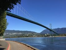 Lions Gate Bridge viewed from Stanley Park Seawall. The Lions Gate Bridge, suspension bridge that crosses the first narrows of Burrard Inlet and connects the royalty free stock photography