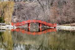 Lions Park Pond Bridge Reflection - Janesville, WI. A reflection of a red bridge going over Lions Park Pond in Janesville, Wisconsin with trees also reflected in royalty free stock image