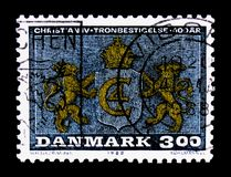 Lions supporting Monogram, King Christian IV - 125th Anniversary of Accession serie, circa 1988. MOSCOW, RUSSIA - OCTOBER 3, 2017: A stamp printed in Denmark Royalty Free Stock Photography