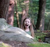 Lions, Tigers, and Daughter. Picture of my daughter in the forest, thought she looked like a wild animal jumping out from behind the rocks Royalty Free Stock Images