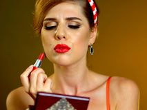 Lip augmentation at home by make up. Girl in pin up retro style do lip augmentation makeup at home . Sexy woman looks in pocket mirror royalty free stock photos