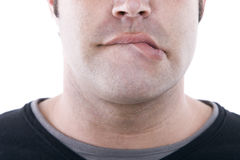 Lip biting. Closeup of the face of a young man bit his lip Royalty Free Stock Photo