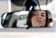Lip gloss in car. A girl sitting in a car makes herself beauty Royalty Free Stock Image