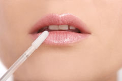Lip gloss close-up. Of an young woman Royalty Free Stock Photos