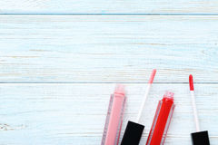 Lip gloss. Colorful lip gloss on blue wooden table Stock Image
