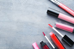 Lip gloss. Colorful lip gloss on grey wooden table Stock Photography