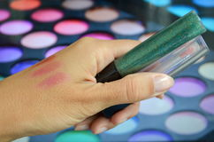 Lip Gloss. Glitter makeup stylist in his hand Royalty Free Stock Image