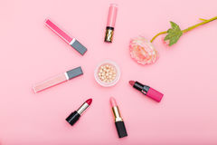 Lip gloss, lipstick and powder and a flower on a pink background Stock Photos