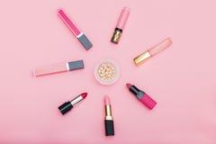 Lip gloss, lipstick and powder on a pink background.flat lay Stock Photo
